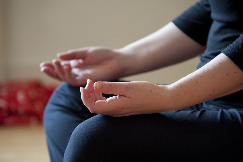 Foto van handen van deelnemer aan meditatie in het Centrum voor Mindfulness Den Haag.