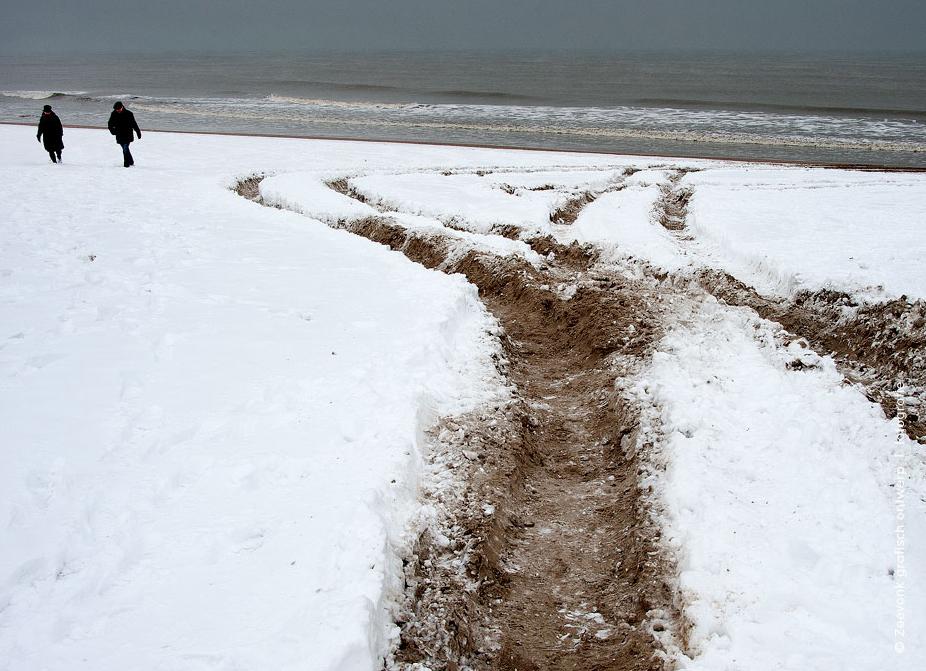 Foto van man en vrouw lopend door de sneeuw tot aan de vloedlijn tijdens strenge winter, Den Haag.