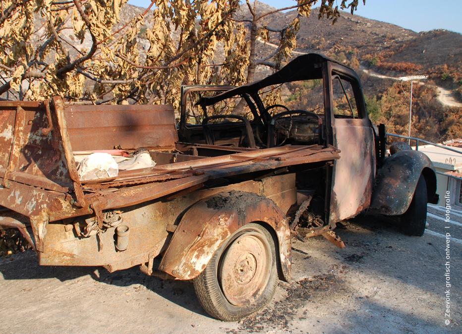 Foto van verbrandde vrachtauto na bosbranden op Kefalonia, Griekenland.
