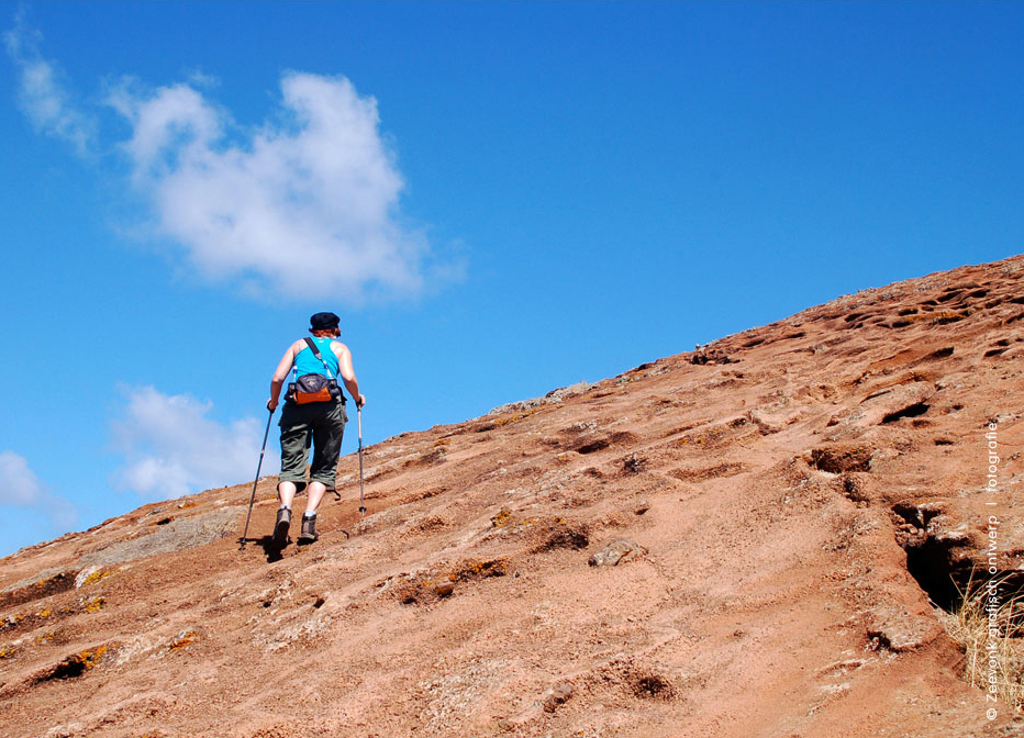 Foto van een vrouw die een berghelling van de Sao Lourenco op Madeira beklimt.