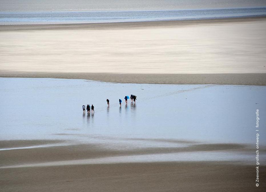 Foto van wadlopers aan de voet van de Mont Saint-Michel, Normandië.