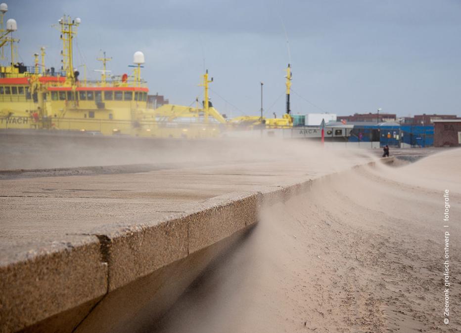 Foto van opwaaiend zand boven het Havenhoofd van Scheveningen, tijdens een zware storm.