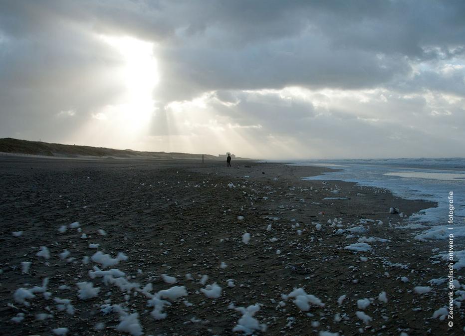 Foto van een doorbrekende zon boven het strand tijdens een zware storm, omgeving Kijkduin.
