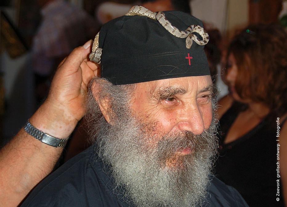 Foto van een Griekse priester met een kleine slang op zijn hoofddeksel, tijdens een slangenfestival op het Griekse eiland Kefalonia.