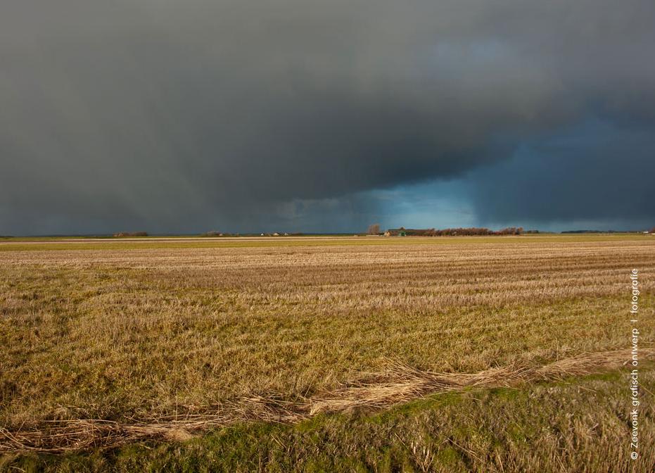 Foto van enorme hagelbui aan de horizon boven akkers op Texel.
