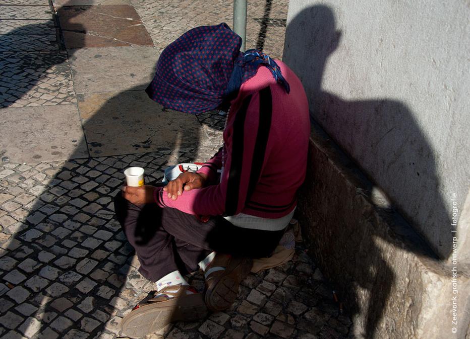 Foto van een bedelaar in de straten van Lissabon, Portugal.