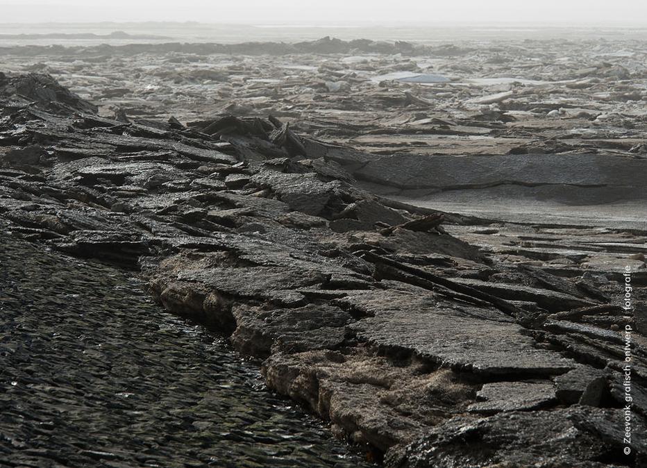 Foto van kruidend ijs dat er uit ziet als brokken asfalt, langs de Afsluitdijk.