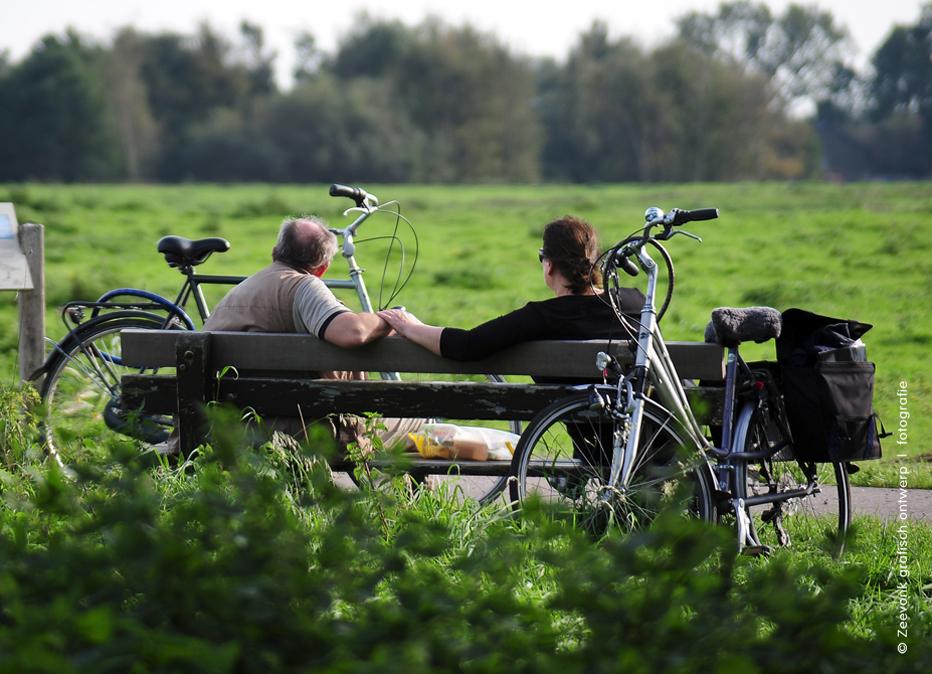 Foto van een man en vrouw die uitrusten op een bankje, tijdens een fietstocht in de omgeving van de Ackerdijkse Plassen.