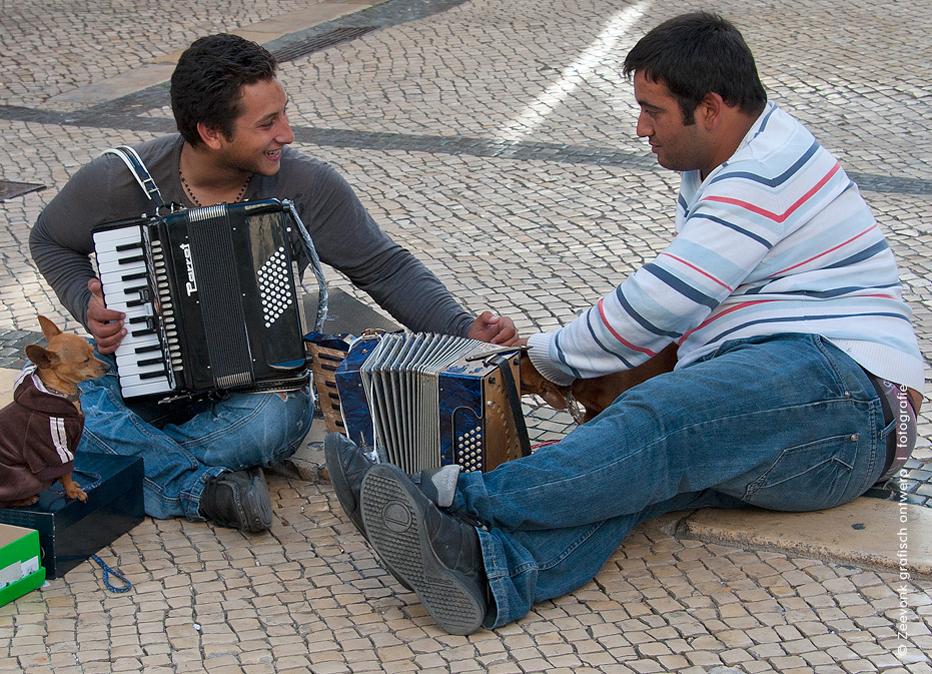 Foto van 2 straatmuzikanten met hun hondje op de boulevard in Lissabon, Portugal.