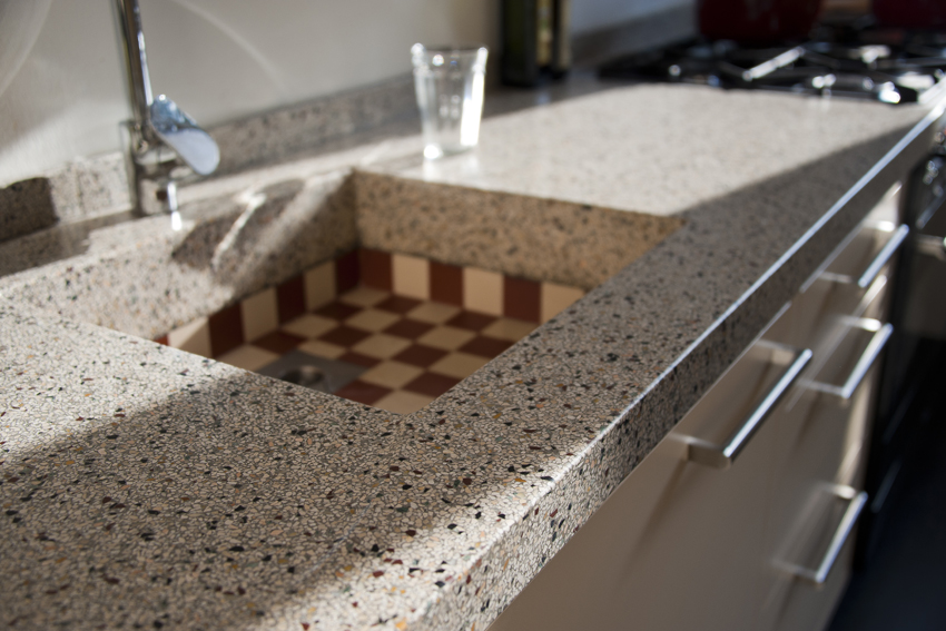 Foto van de gootsteen van een handgemaakte keuken met een aanrecht van terrazzo.