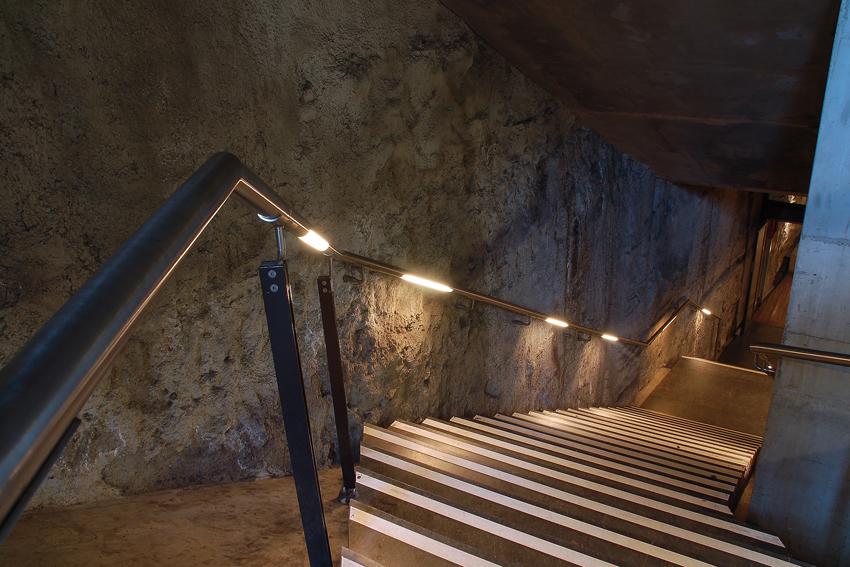 Foto van verlichting de armleuning van een trap van de tramtunnel in Den Haag.
