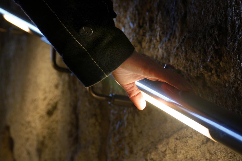 Foto van een hand bij de verlichting van de armleuning van een trap van de tramtunnel in Den Haag.