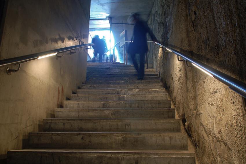 Foto van vrouw die de trap afloopt naar de Haagse tramtunnel.