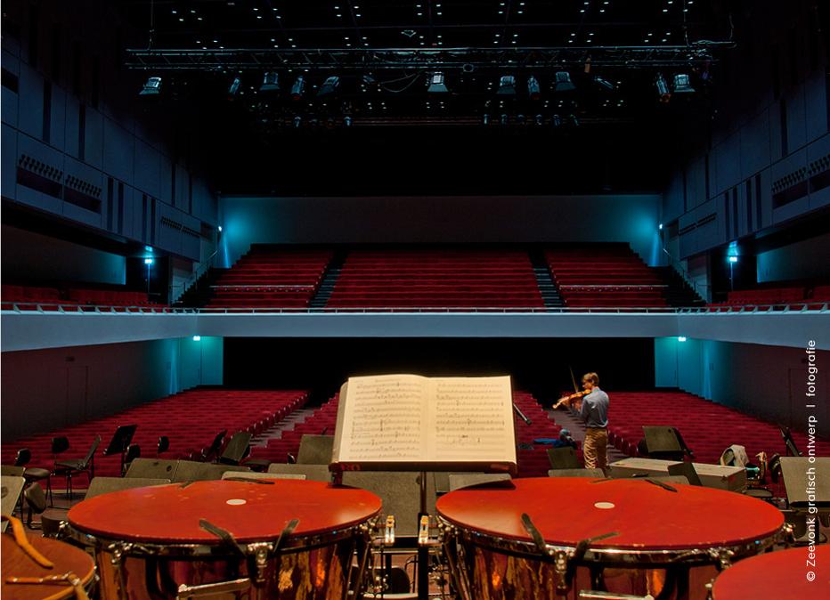Foto van percussieinstrumenten op het toneel, terwijl een violist repeteert in de Anton Philipszaal, Den Haag.