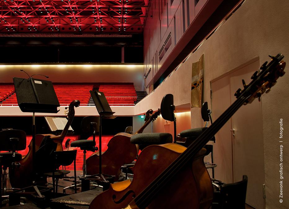 Foto van snaarinstrumenten op het toneel, tijdens een lichtscene in de Anton Philipszaal, Den Haag.